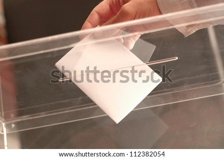 hand putting ballot in the box - stock photo