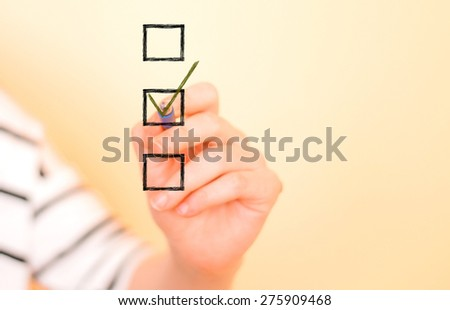 Hand putting check mark with pen