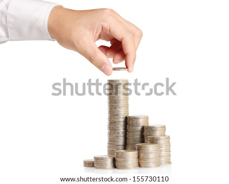 Hand putting coin in stack - stock photo