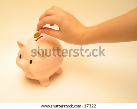 Hand putting coin into piggy bank.