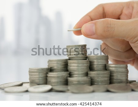 Hand putting coin on coins stack with city background. Savings, Finance , Business Investment Growth Concept.