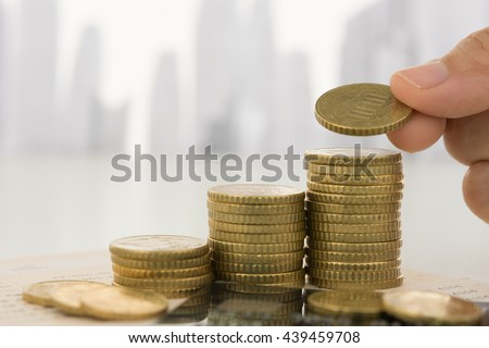 Hand putting coin on coins stack with city in background. Savings, Finance and Banking, Investment Growth Concept.