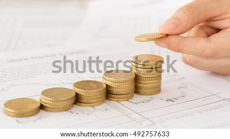 Hand putting coin on coins stack with the finance report . Concepts of investment management, savings planning.
