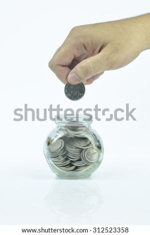 Hand putting coin to the small jar contain coins . Selective focus