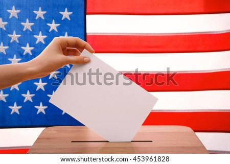 Hand putting down voting paper into a ballot box on American flag background - stock photo