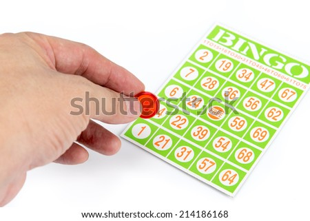 hand putting first chip to bingo game card isolated on white background - stock photo