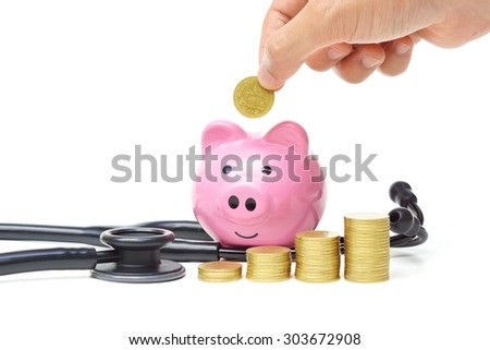 hand putting golden coins into a piggy bank with a stethoscope - stock photo
