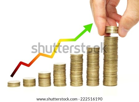 hand putting golden coins to piles of coins arranged as a graph with green arrow               - stock photo