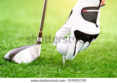 Hand putting golf ball on tee with club in golf course - stock photo