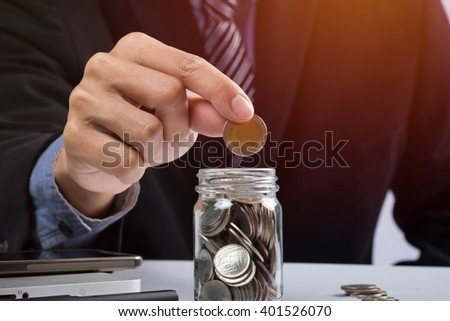 Hand putting mix coins and seed in clear bottle and copyspace, Business investment growth concept. - stock photo