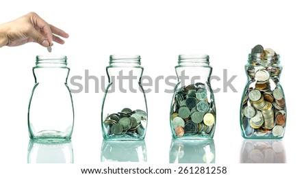Hand putting mix coins in clear bottle on white background,Business investment growth concept - stock photo