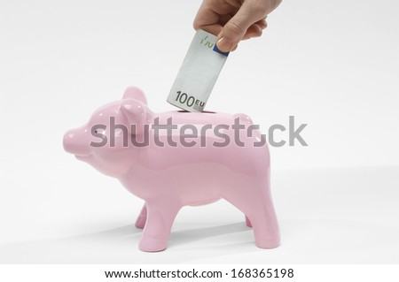 Hand Putting Money in Piggy Bank - stock photo