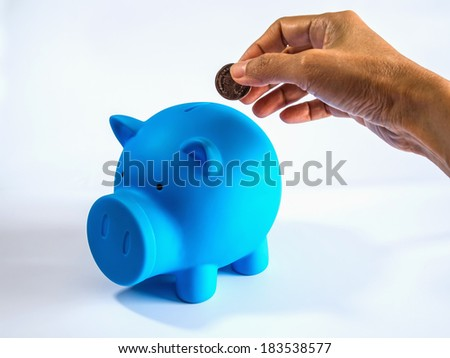 Hand putting money into blue piggy bank on white isolated background