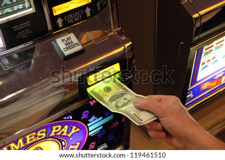 hand putting money into slot machine in Las Vegas - USA - stock photo