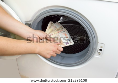 hand putting money into the laundry machine in  concept crime of Money Laundry - stock photo