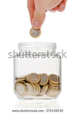 Hand putting one euro coin into money jar isolated on white