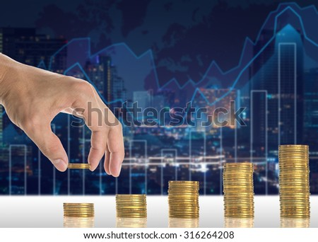 Hand putting the gold coins on the stack of golden coins on Trading graph on the cityscape blurred background, Business financial concept