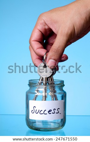 Hand putting the key into the empty jar: The concept of 'Key of success' - stock photo