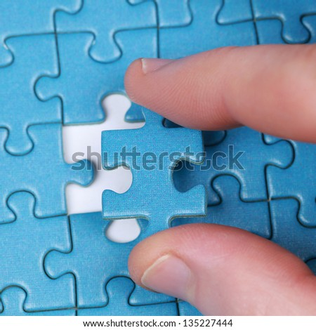 Hand putting the last piece of puzzle in a gap - stock photo