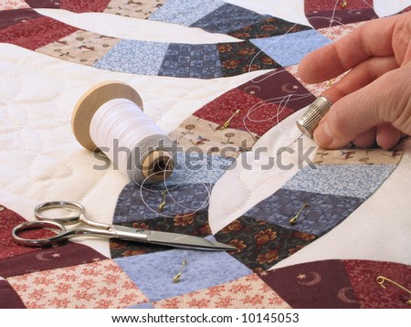 Hand-quilting of a double-wedding ring pattern quilt - stock photo