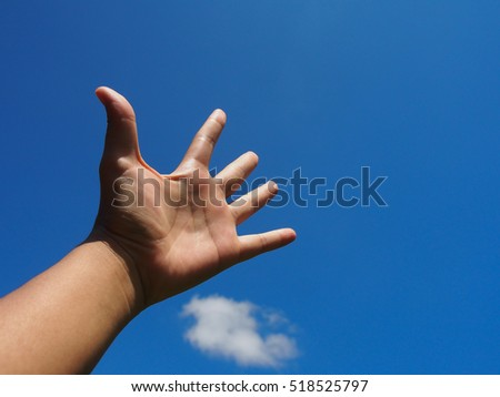 Hand raise up in blue sky with text space.