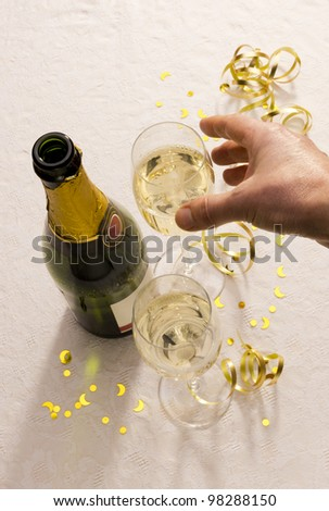 Hand reaches for champagne glasses beside bottle on party table with copy space. - stock photo