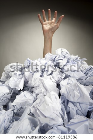 Hand reaches out from big heap of crumpled papers