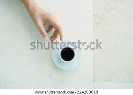 Hand reaching for coffee cup, viewed from directly above - stock photo