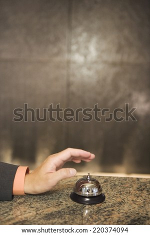 Hand reaching for service bell on counter - stock photo