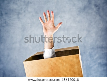 Hand reaching out from the cardboard box and asking for help and salvation. - stock photo