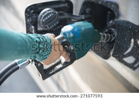 Hand refilling the car with fuel