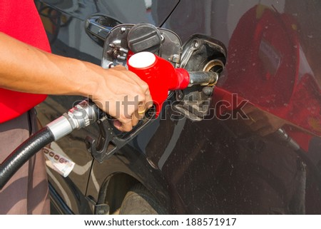 Hand refilling the car with fuel at Petrol pump filling