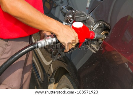 Hand refilling the car with fuel at Petrol pump filling - stock photo
