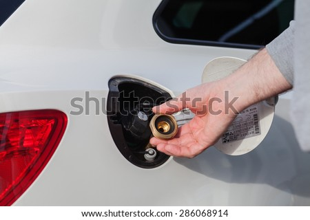 Hand refilling the car with gas