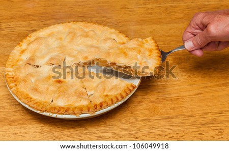 Hand removing slice of freshly baked hot apple pie on wooden table - stock photo
