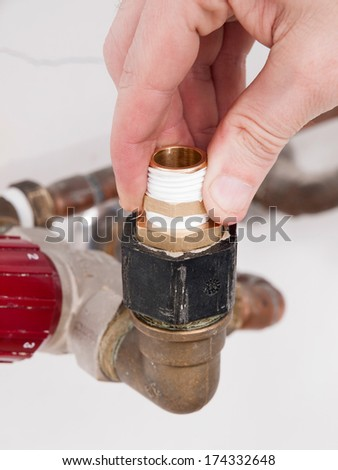 Hand repairing the plumbing pipes of an electric boiler with a spanner - stock photo