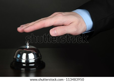 Hand ringing in service bell on wooden table on black background