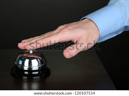 Hand ringing in service bell on wooden table on black background - stock photo