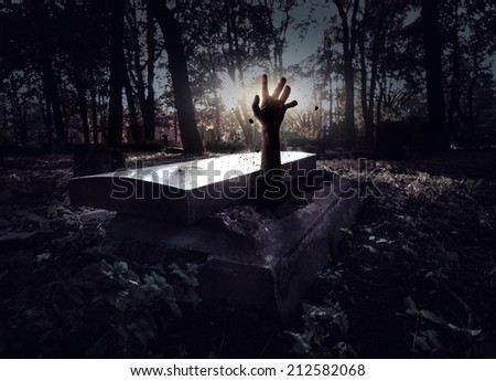 Hand rising out from the grave - stock photo