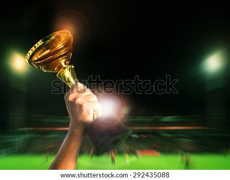 hand rising soccer football championship cup on sport competiton in stadium background - stock photo