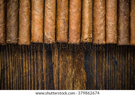 Hand rolled cigars on wooden table, border background, flat view from above. Space for text or advert. - stock photo