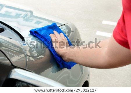 Hand rubbing and polishing car with microfiber cloth