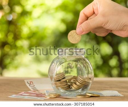 hand's women putting golden coins in money jar. account concept,business concept,finance concept, savings concept. - stock photo