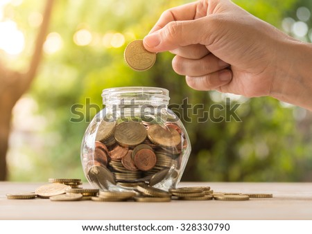 hand's women putting golden coins in money jar. account concept,business concept,finance concept, savings concept. - stock photo