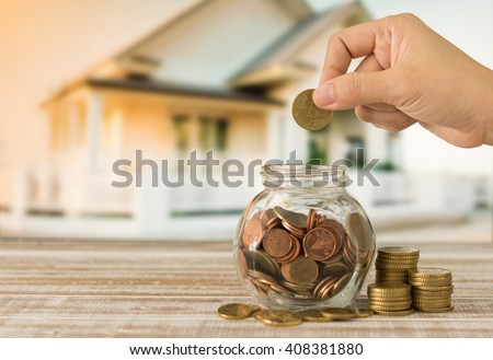 Hand's women putting golden coins in money jar. Concept of real estate investments, Home insurance, Savings plans for housing. - stock photo