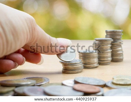 hand saving stack of coins on green nature background