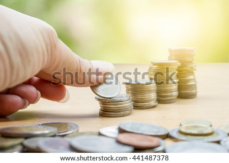hand saving stack of coins with soft sunlight on green nature background