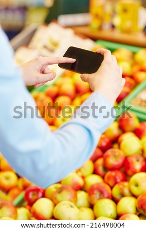 Hand scanning information of fresh fruit with a smartphone in a supermarket - stock photo