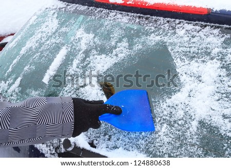 Hand scraping ice from the car window in winter time - stock photo
