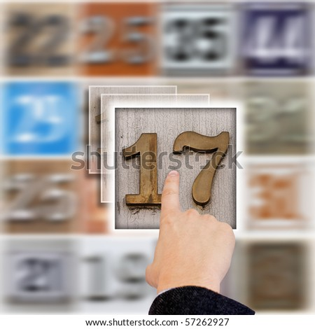 hand select a street number, blured background - stock photo